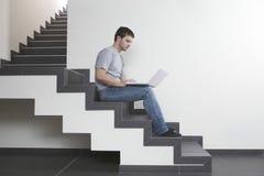 Hombre que usa el ordenador portátil mientras que se sienta en pasos en casa Fotografía de archivo