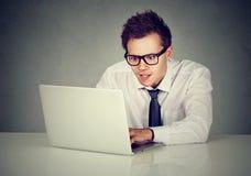 Hombre que usa el ordenador portátil que se sienta en la tabla Imagen de archivo