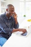 Hombre que usa el ordenador portátil y hablando en el teléfono en cocina en casa Imagen de archivo libre de regalías