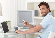 Hombre que usa el ordenador y el teléfono en el país Foto de archivo libre de regalías