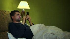Hombre que usa el smartphone para las noticias de lectura en una cama en la noche metrajes
