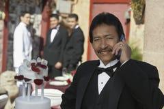 Hombre que usa el teléfono celular en Quinceanera Imagen de archivo