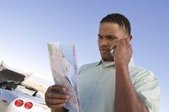 Hombre que usa el teléfono celular mientras que mira el mapa Fotografía de archivo