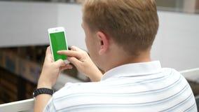 Hombre que usa el teléfono con la pantalla verde usted puede cosechar tan, girar y enfocar fácilmente, sin calidad perdidosa Fáci almacen de video