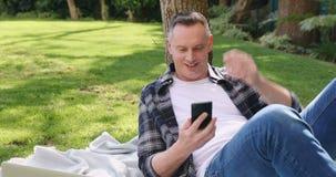 Hombre que usa el teléfono móvil en el jardín 4k almacen de metraje de vídeo