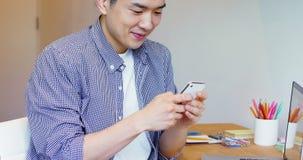 Hombre que usa el teléfono móvil en su escritorio almacen de video