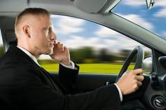 Hombre que usa el teléfono móvil mientras que conduce imagenes de archivo