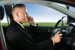 Hombre que usa el teléfono móvil mientras que conduce imagen de archivo libre de regalías