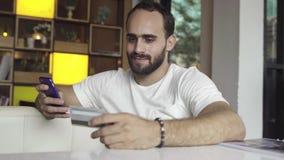Hombre que usa el teléfono móvil para las compras en línea con la tarjeta de crédito fotos de archivo