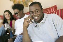 Hombre que usa el teléfono móvil y a amigos con la videocámara Imágenes de archivo libres de regalías