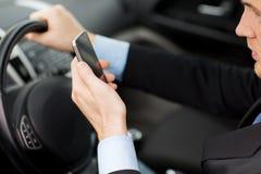 Hombre que usa el teléfono mientras que conduce el coche Fotografía de archivo