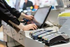 Hombre que usa el terminal de la posición en la tienda que paga la tarjeta de crédito purch fotografía de archivo