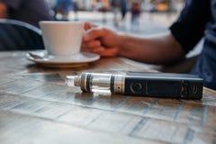 Hombre que usa el vape o el cigarrillo electrónico y bebiendo el café Fotos de archivo libres de regalías