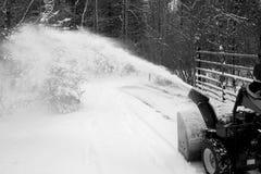 Hombre que usa el ventilador de nieve en calzada Imagen de archivo