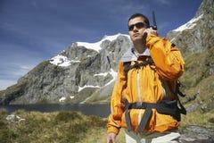 Hombre que usa el Walkietalkie por el lago country Imagen de archivo libre de regalías