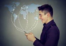 Hombre que usa Internet de la ojeada del smartphone en un fondo mundial del mapa Imágenes de archivo libres de regalías