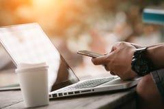 Hombre que usa Internet en el teléfono y el ordenador portátil elegantes Foto de archivo