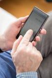 Hombre que usa la calculadora en teléfono Imágenes de archivo libres de regalías