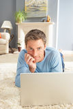 Hombre que usa la colocación de relajación de la computadora portátil en la manta en el país Fotografía de archivo libre de regalías