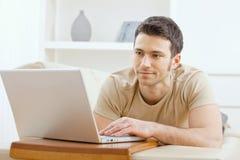 Hombre que usa la computadora portátil en el país Imagen de archivo