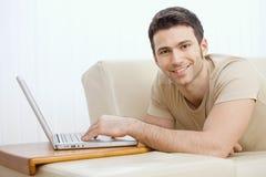 Hombre que usa la computadora portátil en el país Foto de archivo