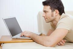 Hombre que usa la computadora portátil en el país Foto de archivo libre de regalías