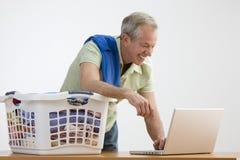 Hombre que usa la computadora portátil mientras que hace el lavadero Fotos de archivo libres de regalías