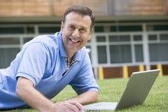 Hombre que usa la computadora portátil mientras que miente en hierba en campus Fotos de archivo libres de regalías