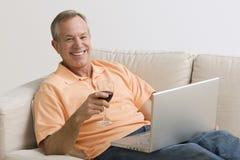 Hombre que usa la computadora portátil y bebiendo el vino Foto de archivo