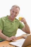 Hombre que usa la computadora portátil y comiendo el desayuno Fotografía de archivo libre de regalías