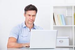 Hombre que usa la computadora portátil Foto de archivo libre de regalías