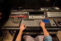 Hombre que usa la consola de mezcla en el estudio de grabación de la música imagenes de archivo