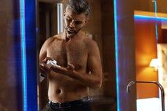 Hombre que usa la crema de afeitar en cara en cuarto de baño Cuidado de piel de los hombres Foto de archivo