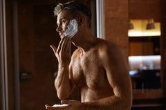Hombre que usa la crema de afeitar en cara en cuarto de baño Cuidado de piel de los hombres Imagenes de archivo