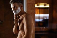 Hombre que usa la crema de afeitar en cara en cuarto de baño Cuidado de piel de los hombres Imagen de archivo libre de regalías