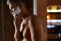 Hombre que usa la crema de afeitar en cara en cuarto de baño Cuidado de piel de los hombres Fotos de archivo libres de regalías