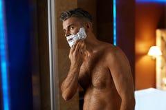 Hombre que usa la crema de afeitar en cara en cuarto de baño Cuidado de piel de los hombres Imágenes de archivo libres de regalías