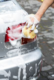 Hombre que usa la espuma para el coche de limpieza Imagen de archivo