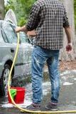 Hombre que usa la manguera de jardín para limpiar Imagen de archivo libre de regalías