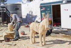 Hombre que usa la motosierra para tallar una talla de madera del burro Imágenes de archivo libres de regalías