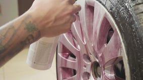 Hombre que usa la química para la rueda de coche deportivo de limpieza, cámara lenta almacen de metraje de vídeo