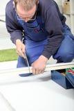 Hombre que usa la sierra para metales imagen de archivo