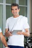 Hombre que usa la tableta de Digitaces en club de salud Fotografía de archivo