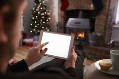 Hombre que usa la tableta de Digitaces en el sitio adornado para la Navidad imagen de archivo