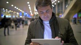 Hombre que usa la tableta electrónica en la estación metrajes