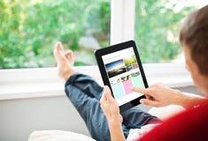 Hombre que usa la tableta en el sofá Imagenes de archivo