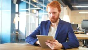 Hombre que usa la tableta en la oficina, pelos rojos almacen de video