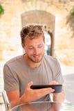 Hombre que usa la tableta 4g app que trabaja en café al aire libre Foto de archivo