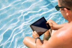 Hombre que usa la tableta por la piscina Imágenes de archivo libres de regalías