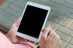 Hombre que usa la tableta que se sienta en el banco en el parque imagenes de archivo